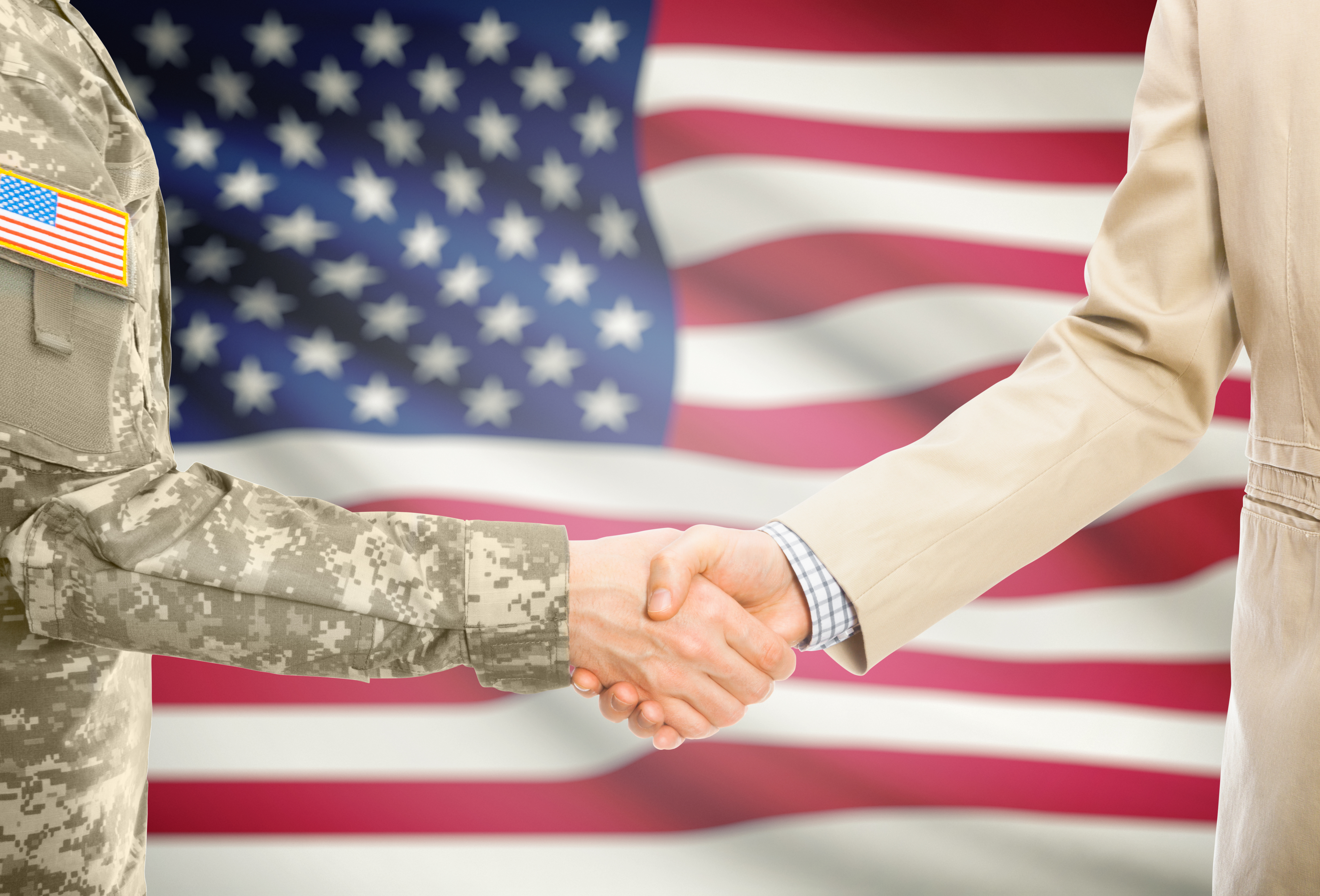 USA military man in uniform and civil man in suit shaking hands with national flag on background – United States